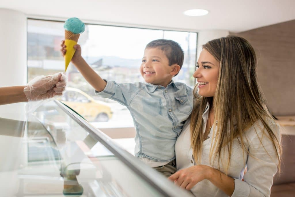Happy woman holding a happy child who is grabbing some ice cream from an ice cream shop.