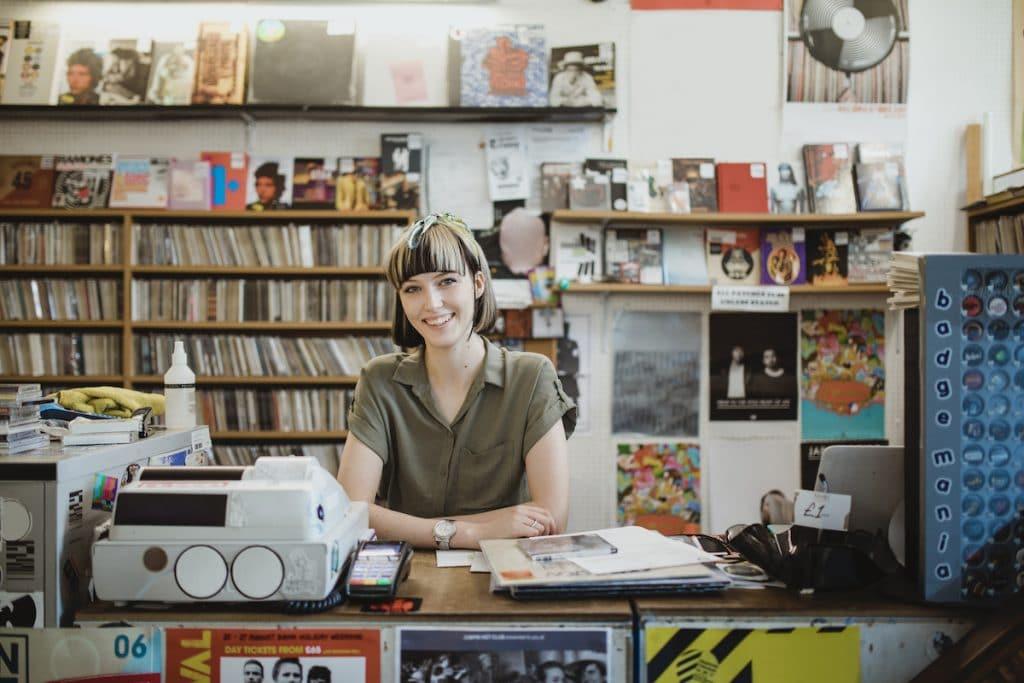 A smiling woman at a cash register of a record shop.