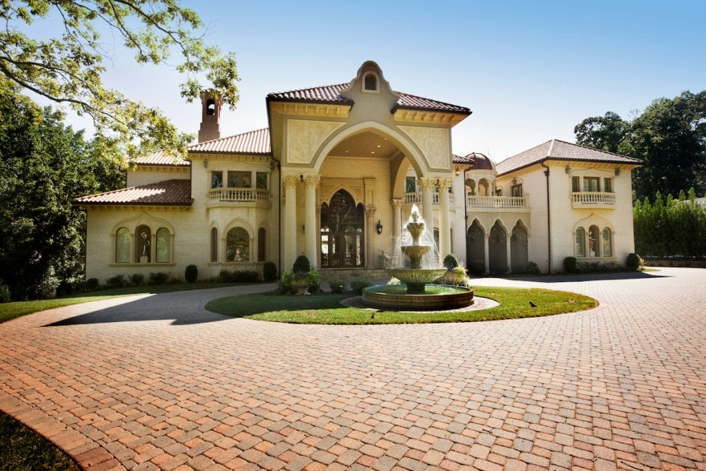 A large house with a brick driveway and fountain in the front.