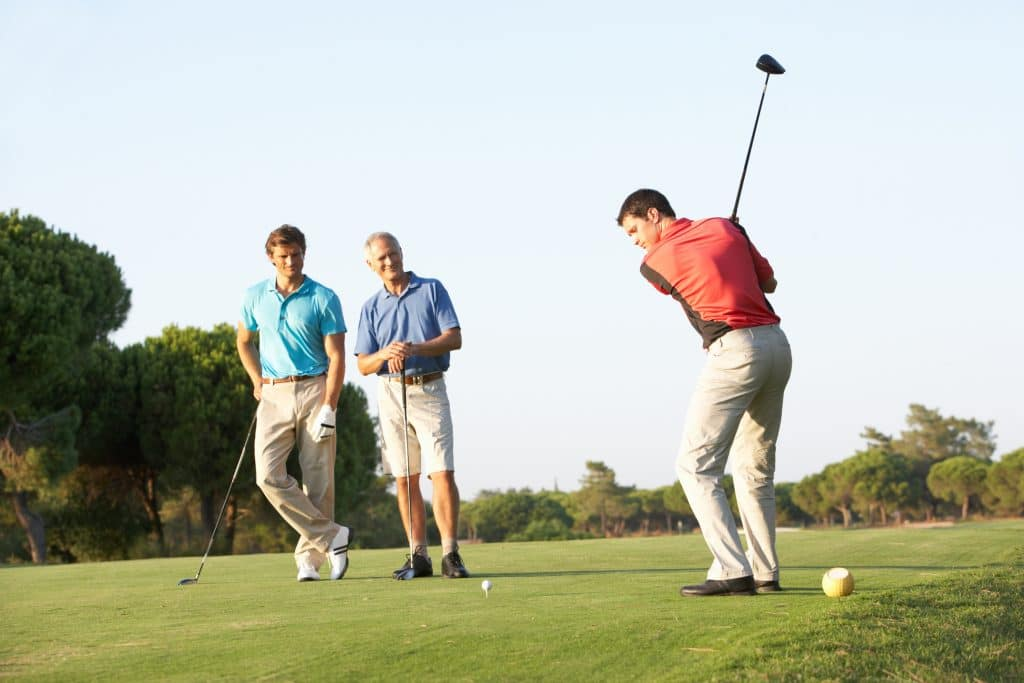 One man swinging a golf club while two men watch on a golf course.