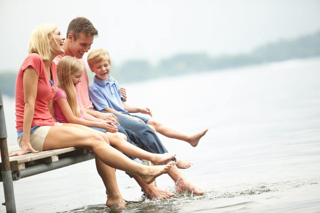 A happy caucasian family dipping their toes in a lake.