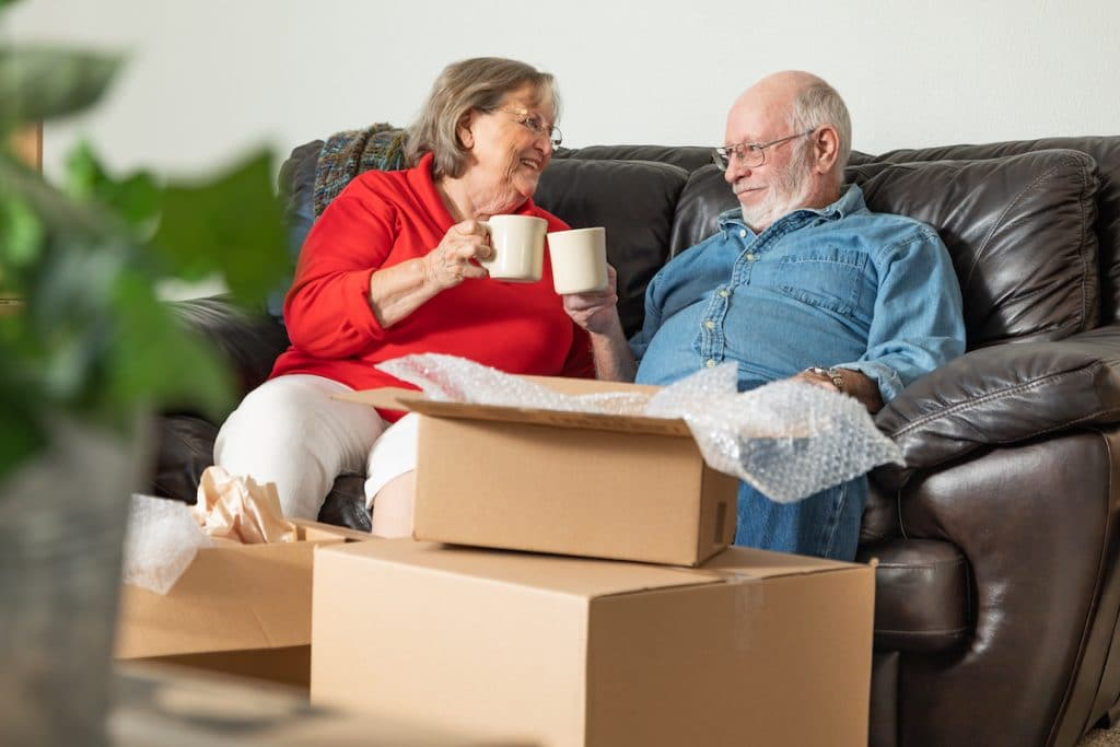An elderly couple sitting on a couch drinking coffee with moving boxes around them.
