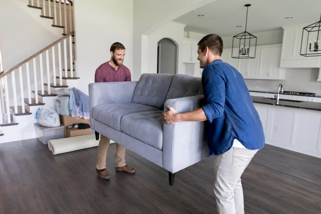 Two men lifting a couch.