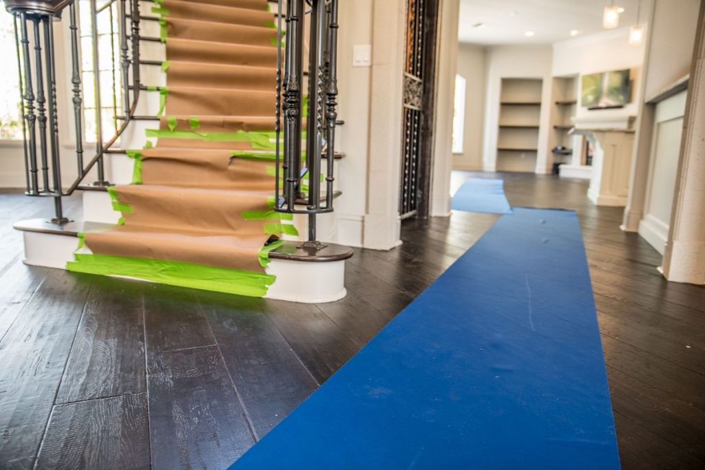 A staircase properly protected along with floor runners to protect the floor.