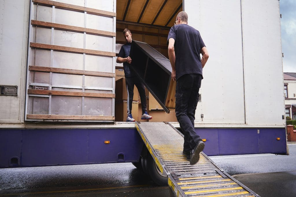 Two men moving furniture out of a moving truck.