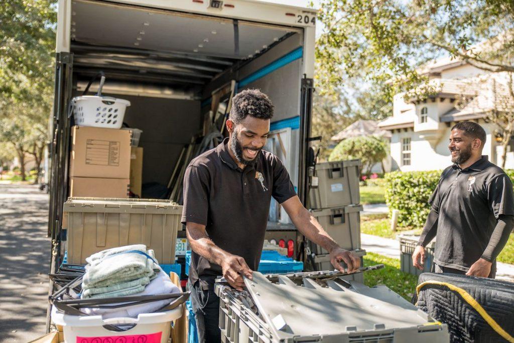 African American and Hispanic members of the Megan's Moving team unloading a moving truck.