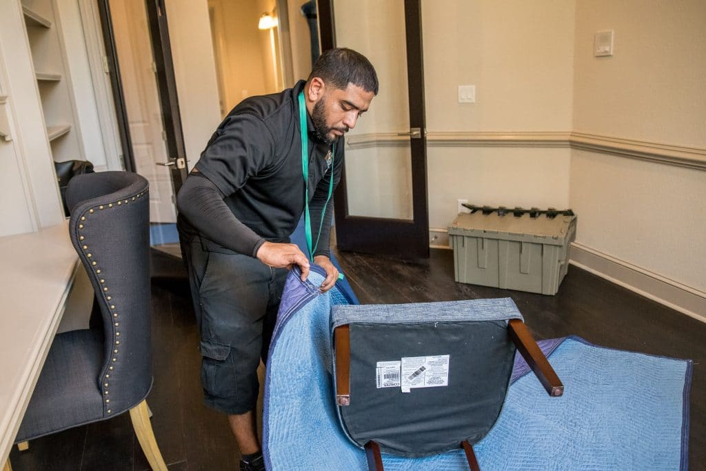 Hispanic male from Megan's Moving team wrapping a chair with a moving blanket.