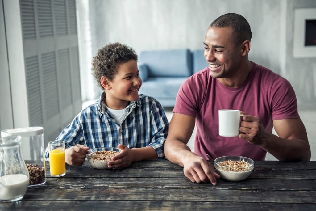 African American man and son eating cereal.