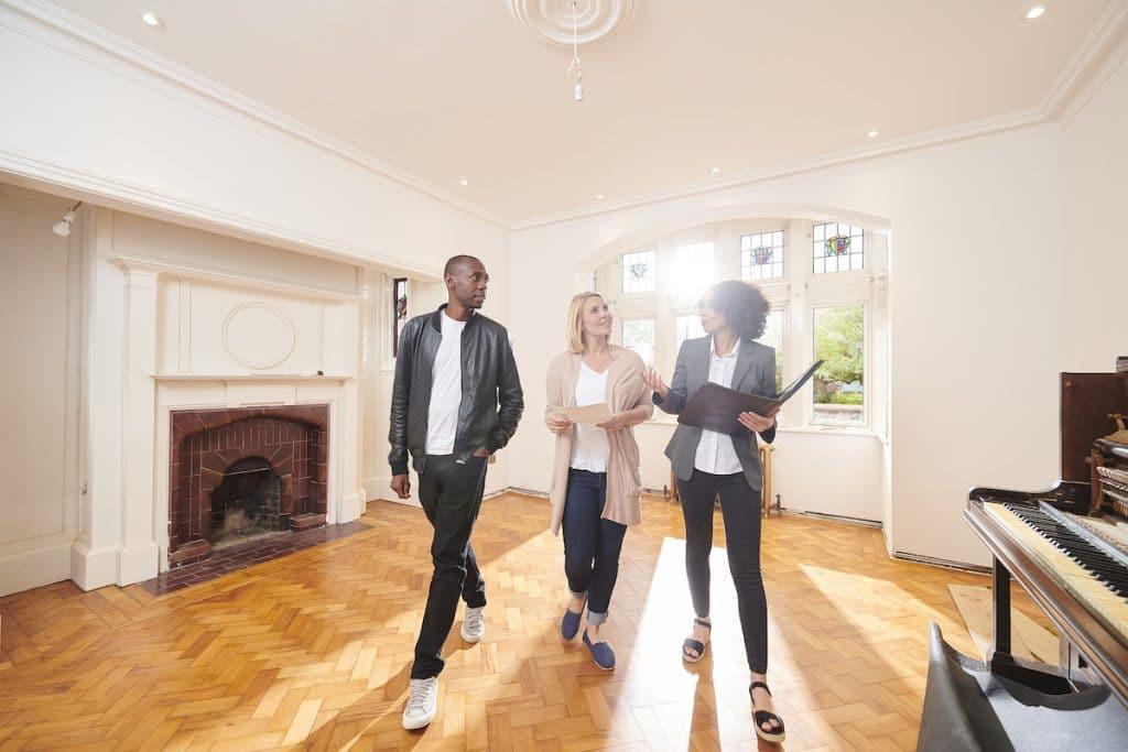 A woman is walking through a biracial couple through a home with a piano.