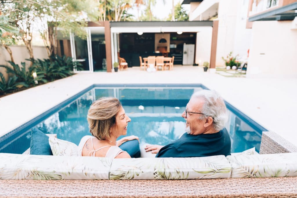 An elderly couple sitting on patio furniture by their pool.