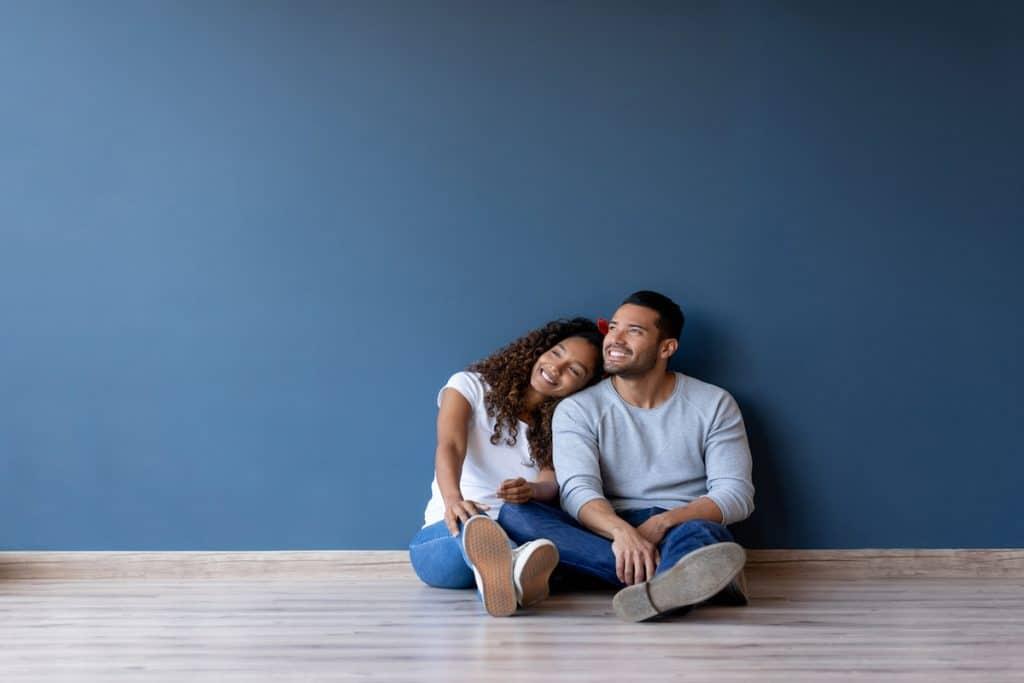Happy hispanic couple sitting on the floor of an empty room.
