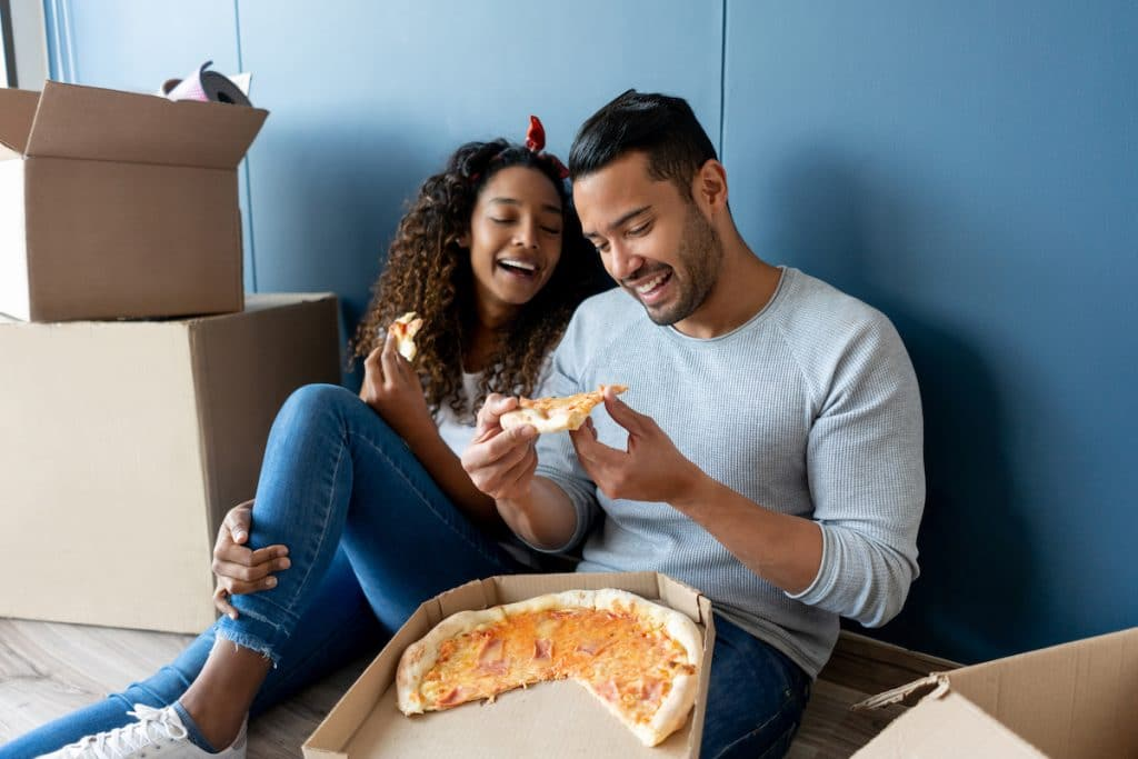 A happy biracial couple eating pizza while sitting on a floor surrounded by boxes.