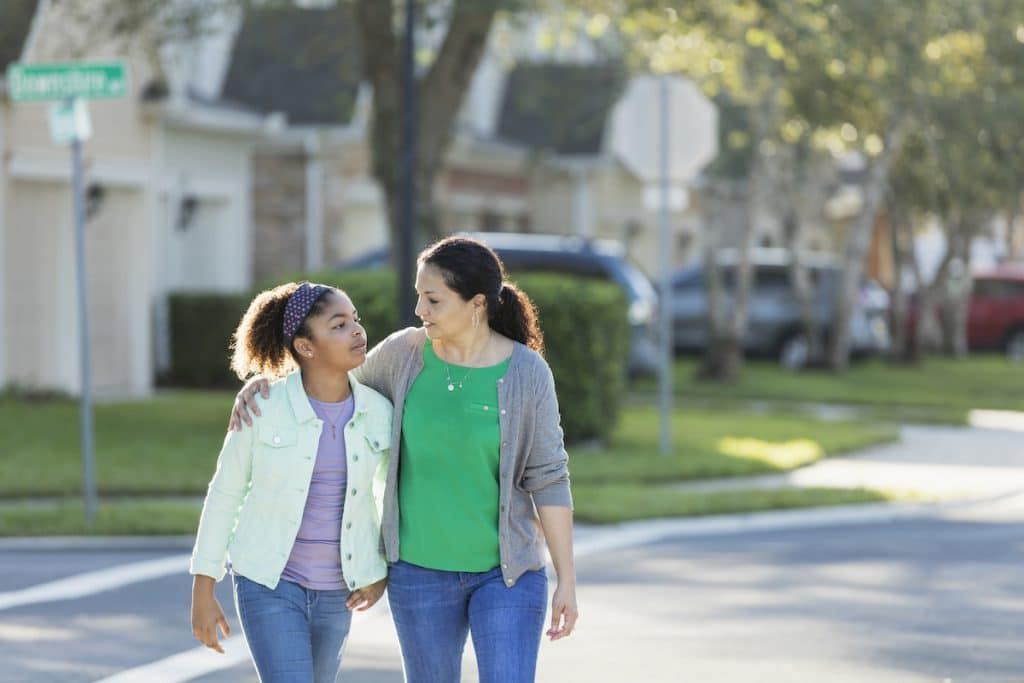 Mature hispanic woman walking with young girl.