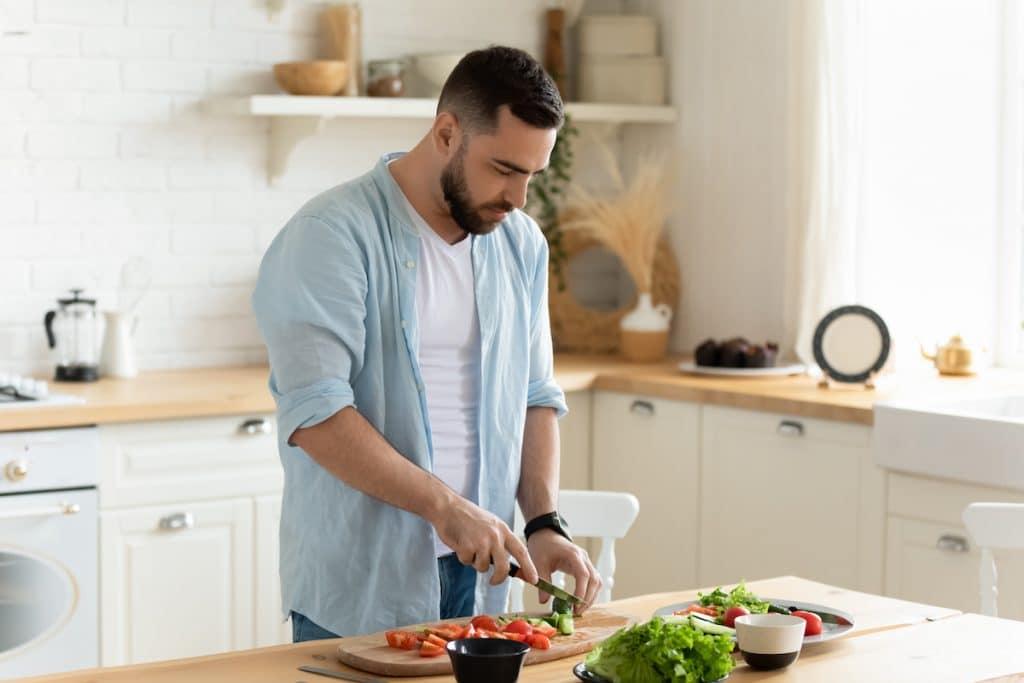 Young man chopping veggies in a kitchen.