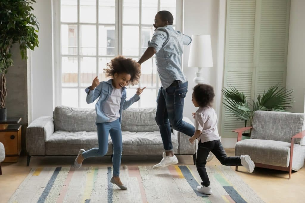Happy African American dad with two children dancing in their living room.