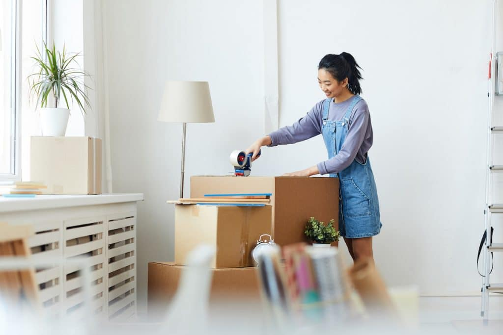 A happy Asian woman sealing a moving box.