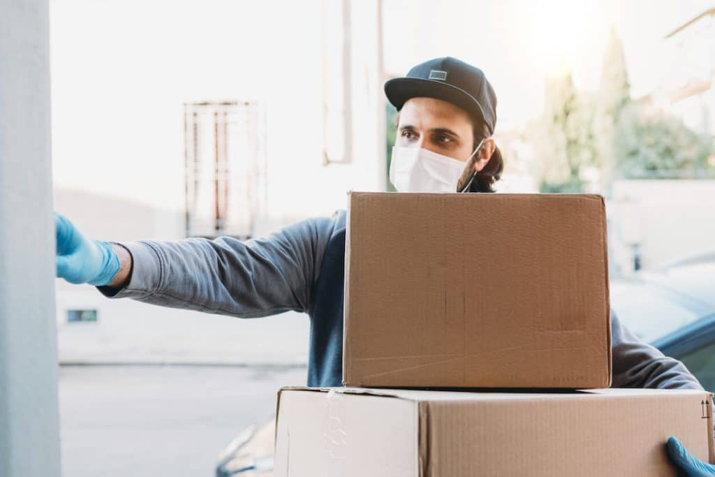 A masked man carrying stacked boxes.
