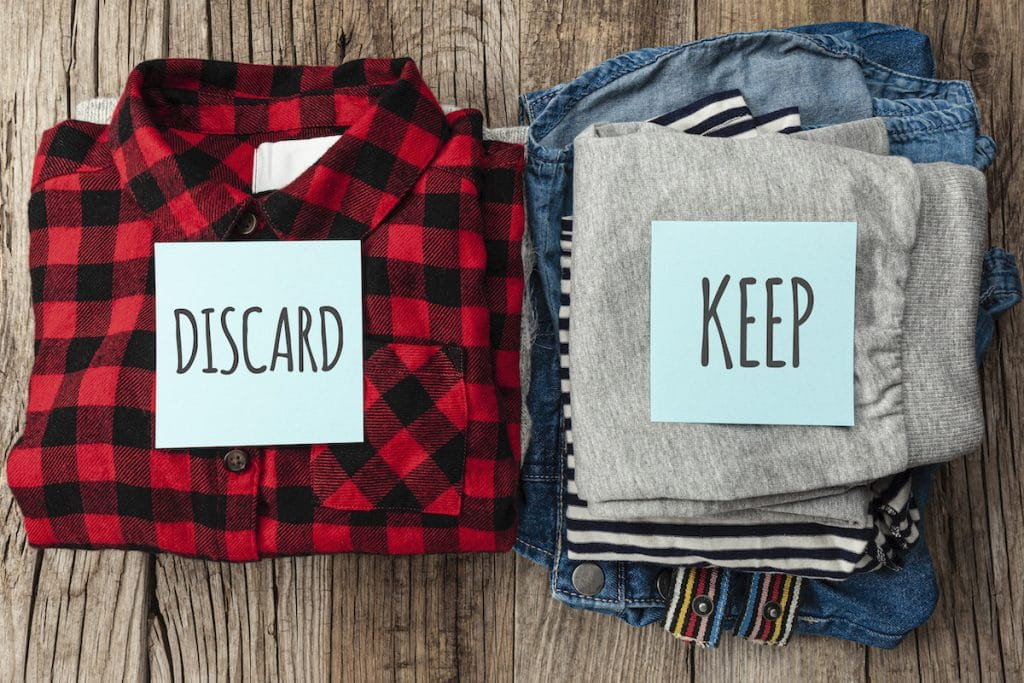 Two piles of clothes each with a sticky note — one that says discard and another that says keep.
