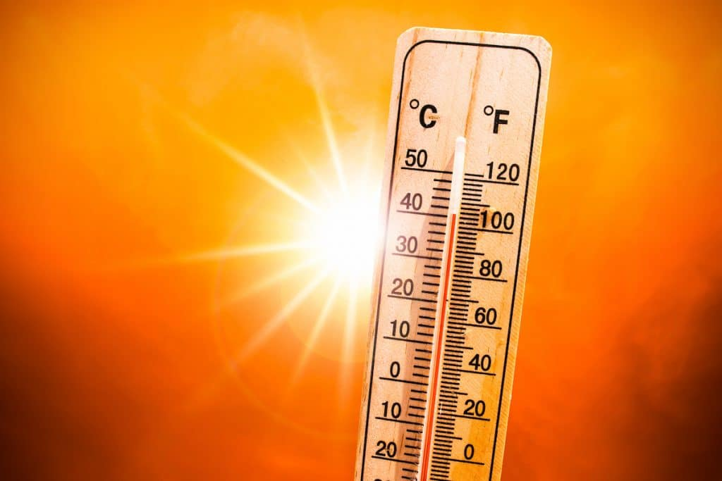 Close-up of a thermometer with the sun blazing in the background.