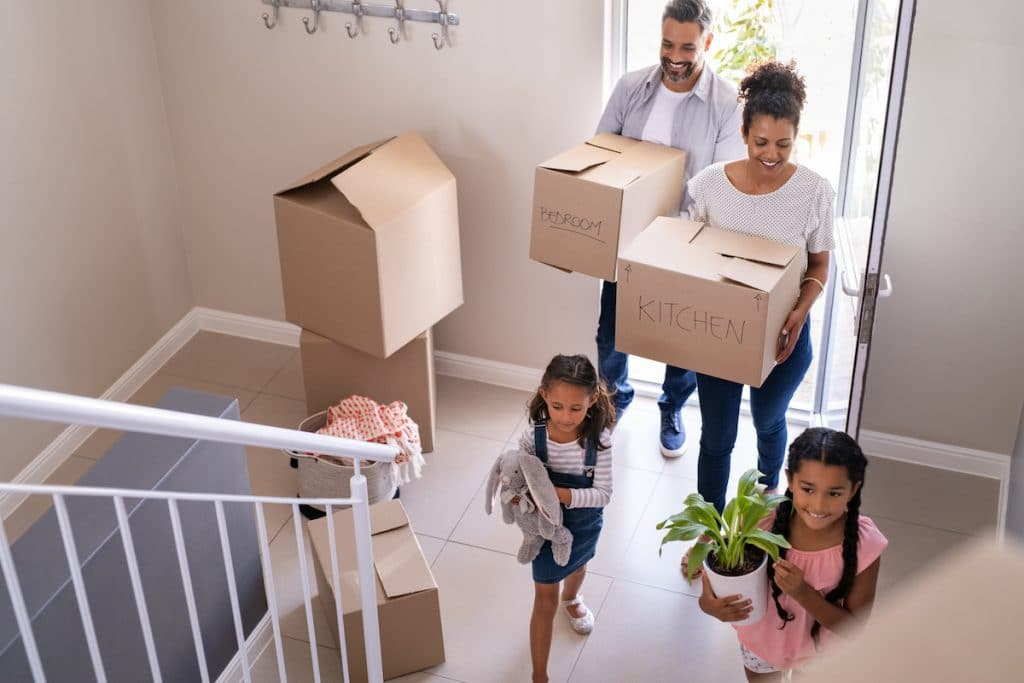 A multiethnic family carrying in boxes into a home.