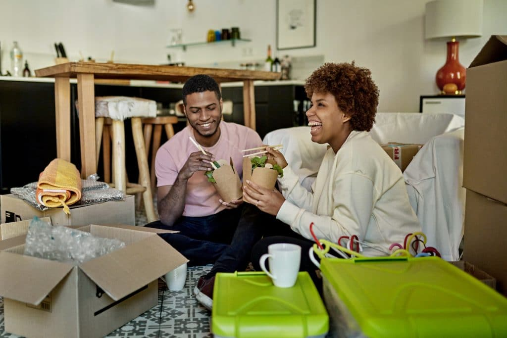 A happy African American couple eating salad while sitting on the floor with boxes surrounding them.