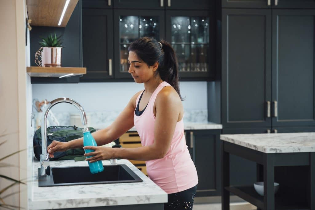 An Indian woman filling up a water bottle at her sink.