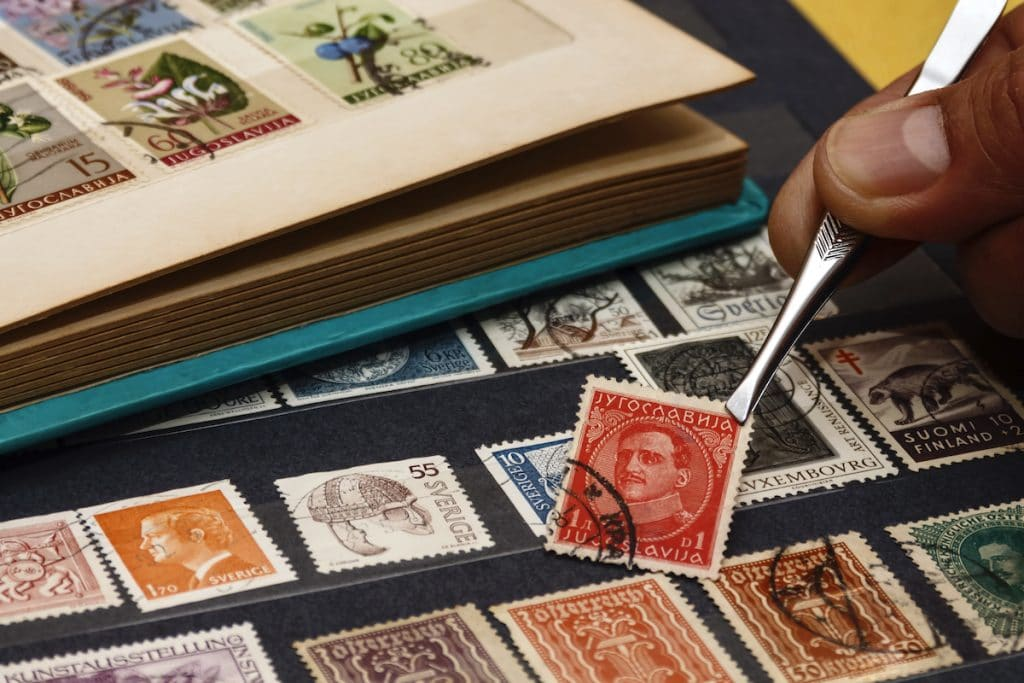 Closeup of someone adding a stamp to their collection.