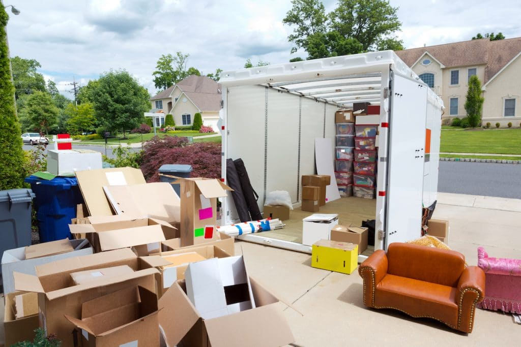 An on-site storage unit with many boxes in front of it.