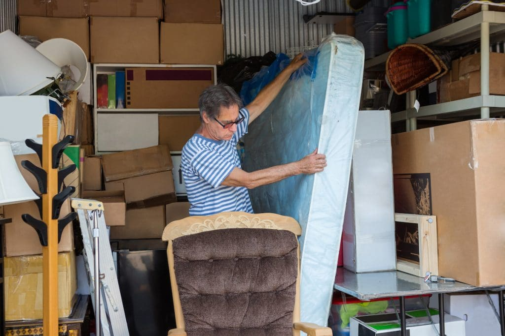 An elderly male packing things inside a storage unit.