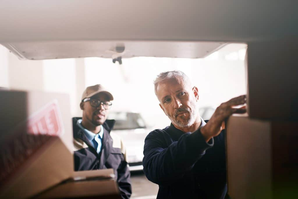 An elderly male and African American man loading boxes.