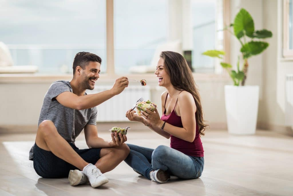 Happy man feeding his girlfriend salad on floor of new home.