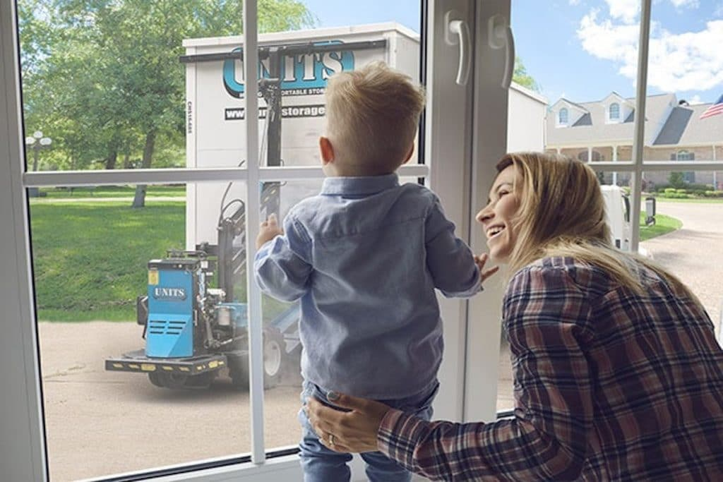 A blonde woman smiling at her toddler who is staring out the window with a UNITS storage container in view.