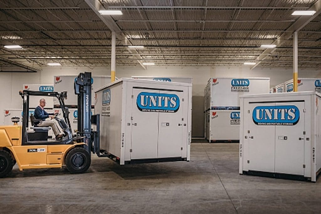 A UNITS storage container being moved inside a facility by machinery.