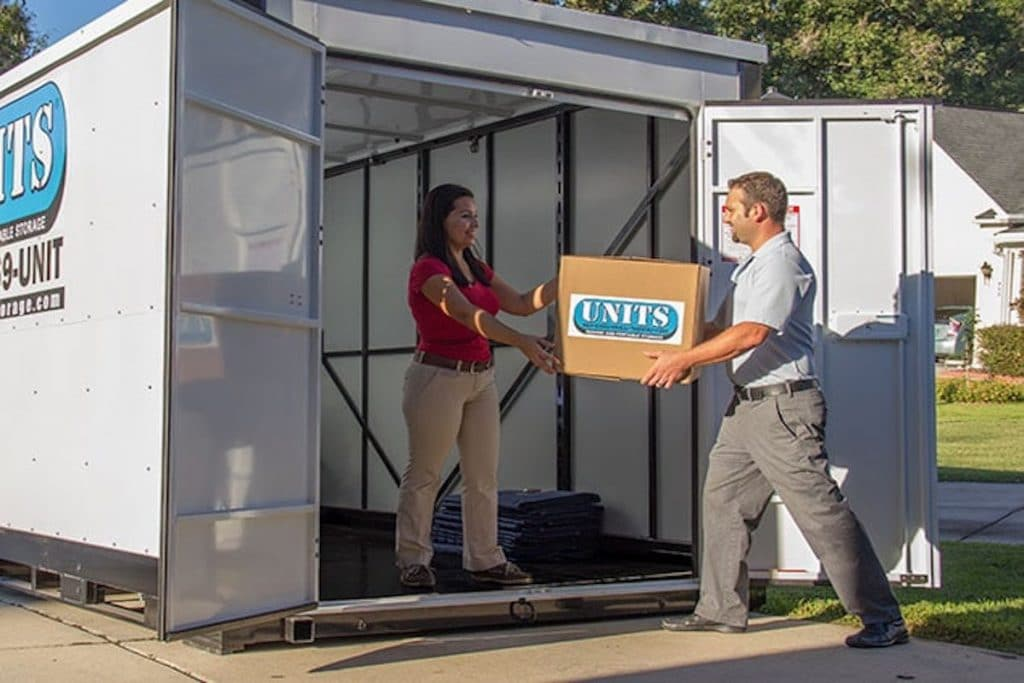 A man handing a box to a woman inside a UNITS storage container.