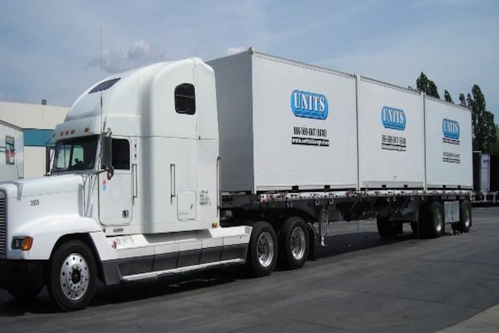 A UNITS truck carrying three storage containers.