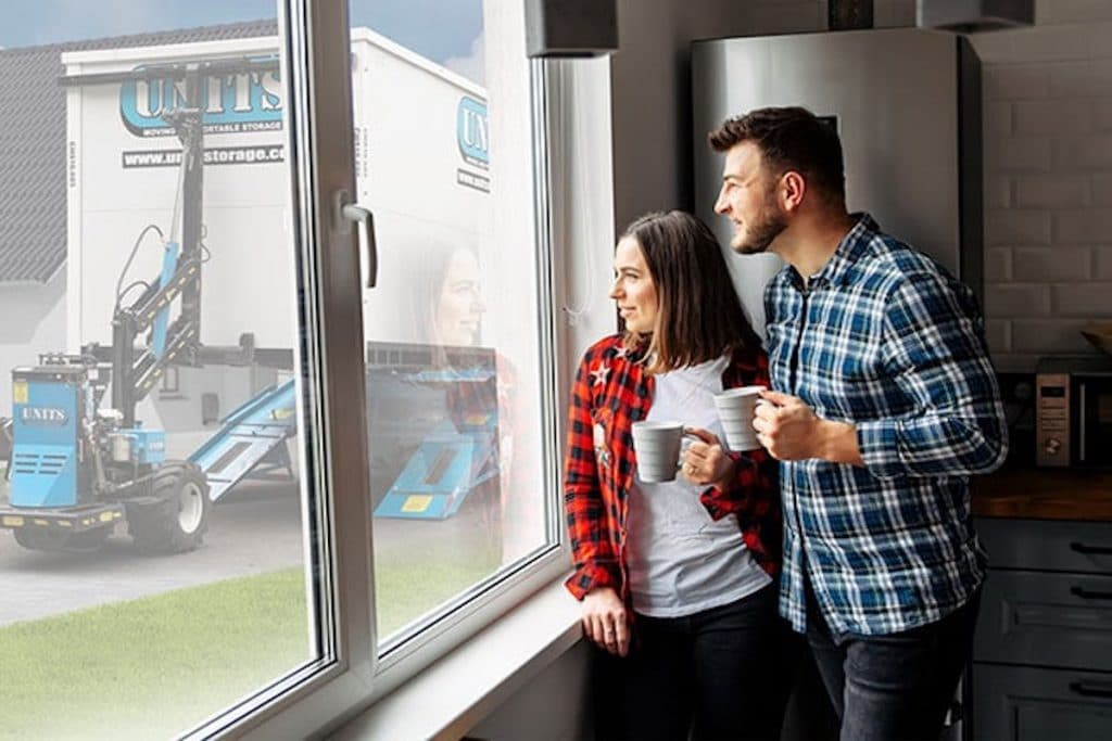 A man and woman looking outside the window holding mugs with a UNITS storage container in sight.
