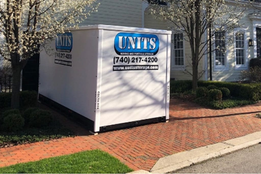 A UNITS storage unit in front of a house.