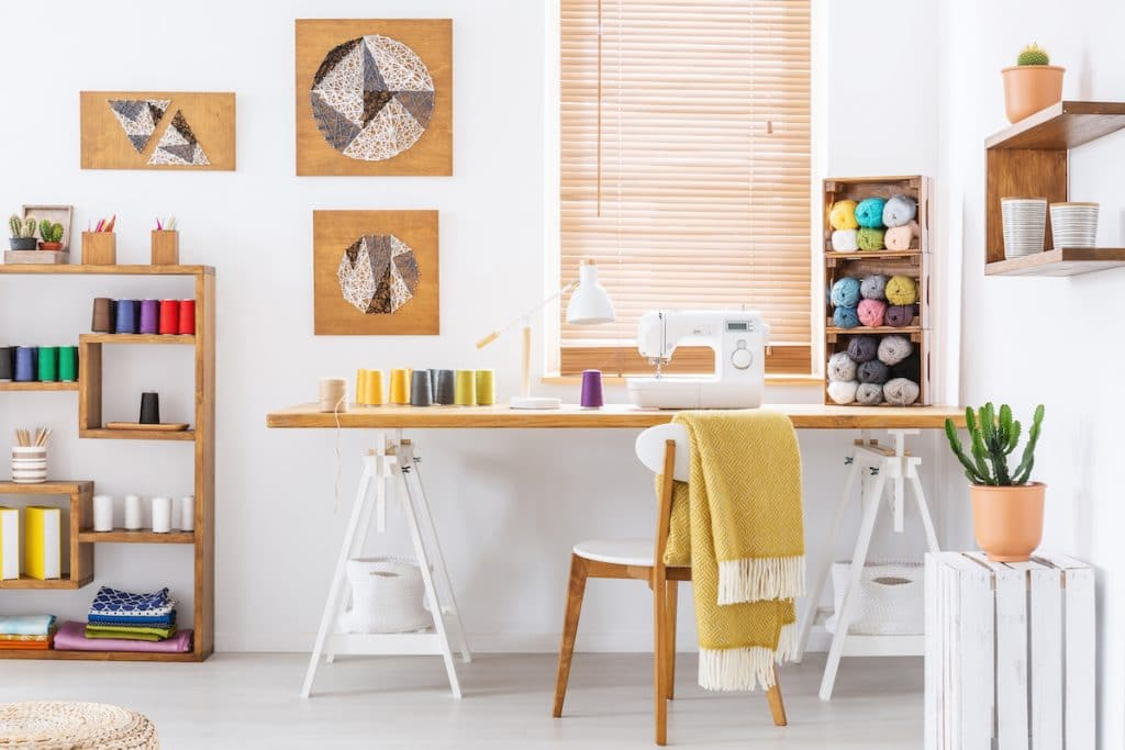 A sewing room with sewing table and shelves with supplies on them.