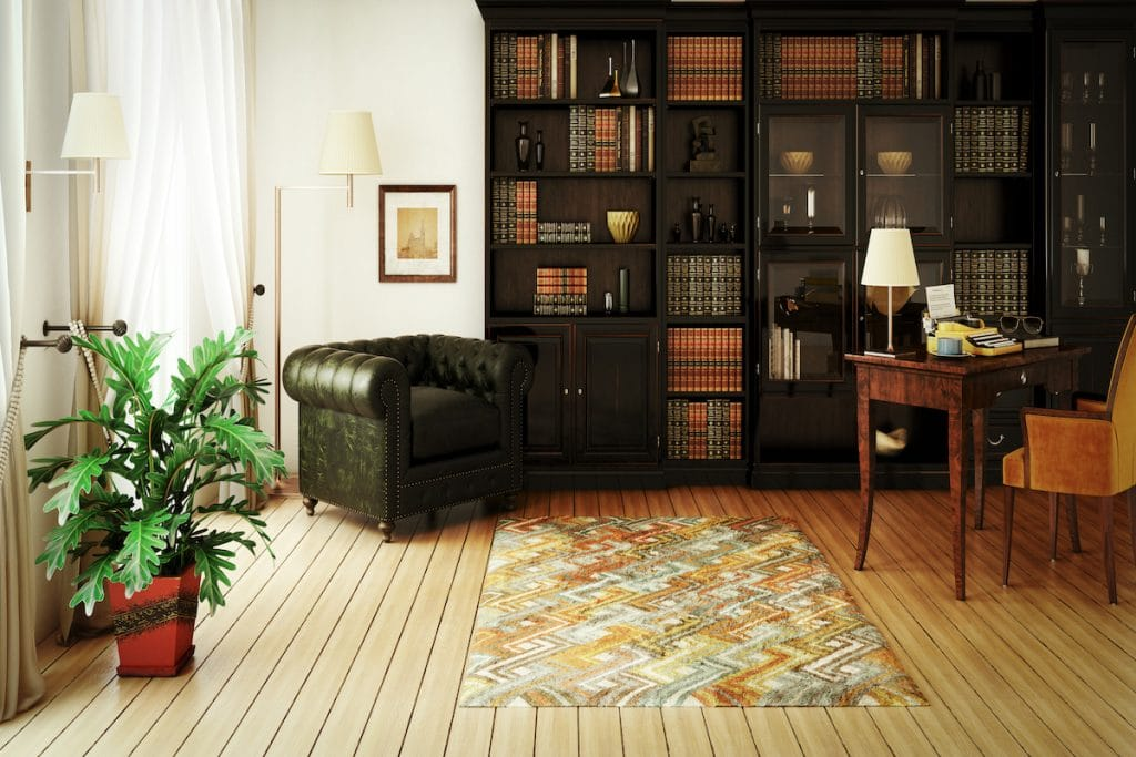 A home library with a club chair, plant, and plenty of bookshelves.