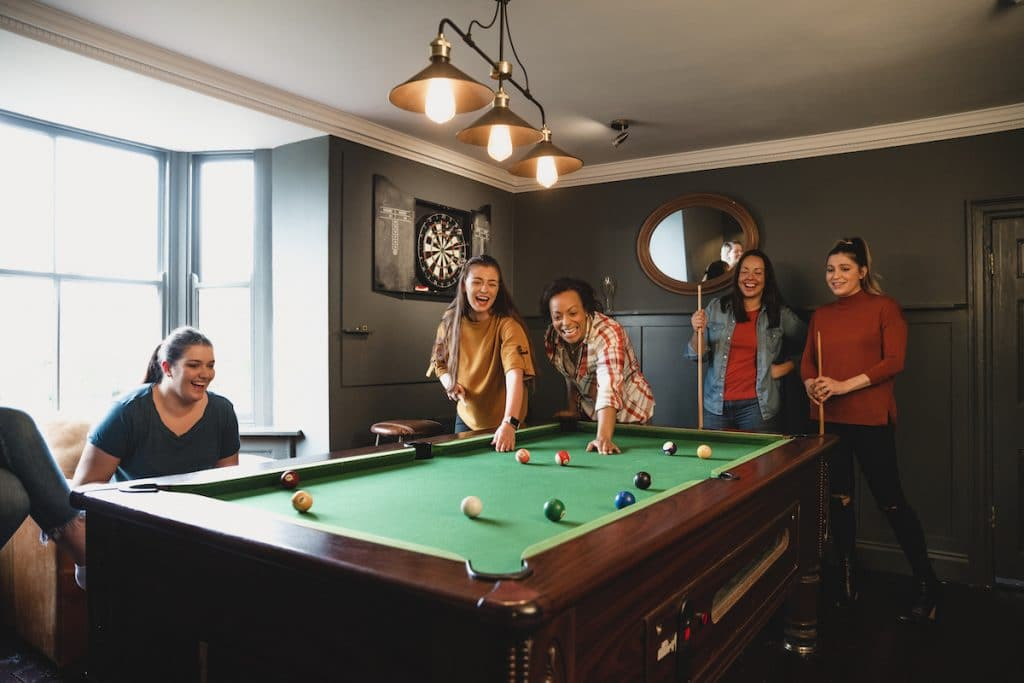 A group of ladies in a room playing pool.