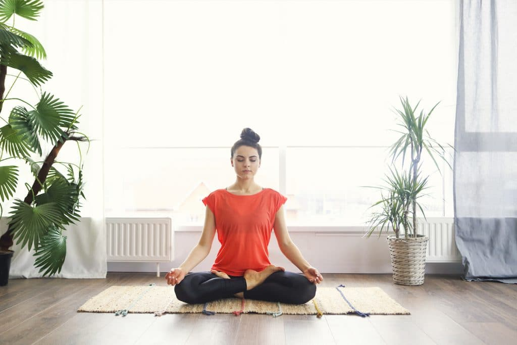 A woman in a meditation pose on a mat with plants around her.
