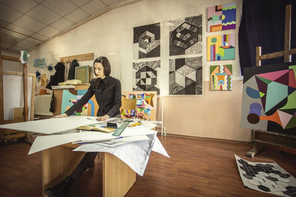 A woman working in her art studio with artwork on the walls.