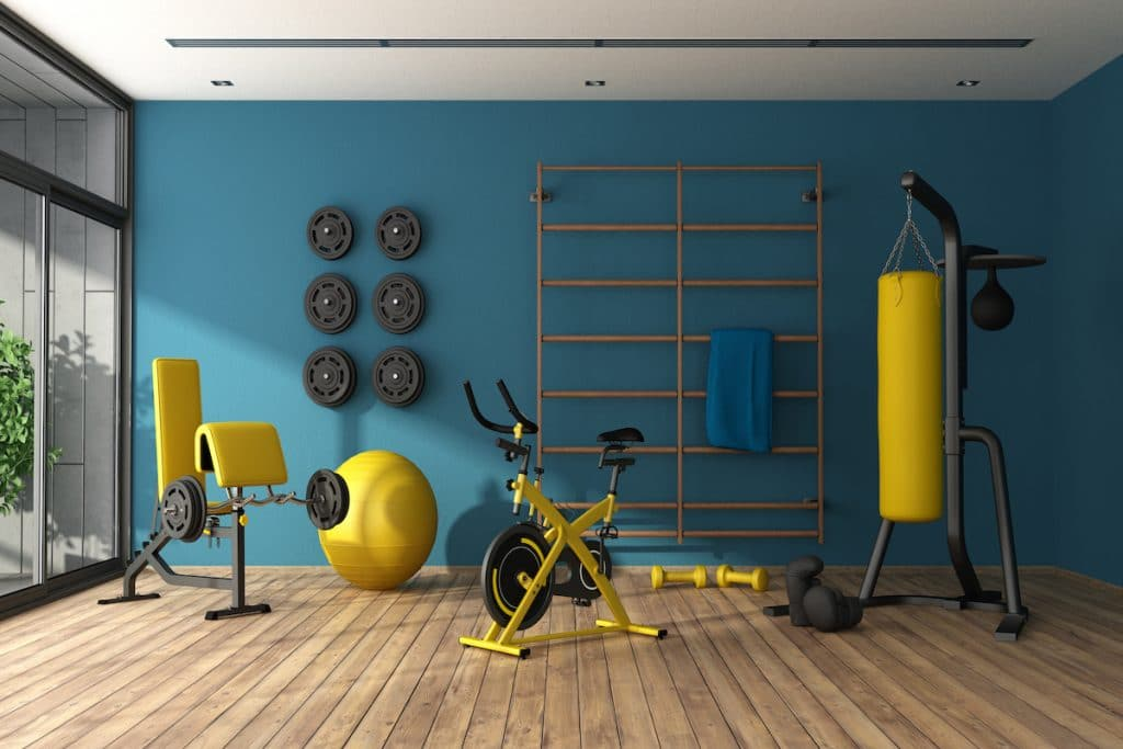 A fitness room with exercise equipment and wights hung on the wall.