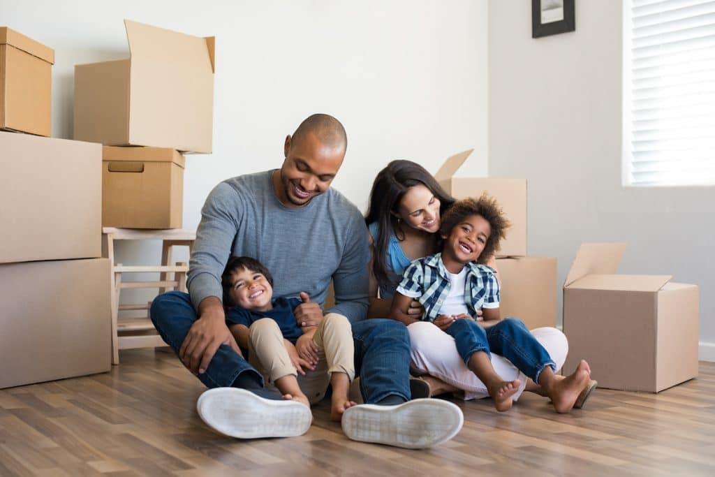 A happy multiethnic family sitting on the floor with moving boxes surrounding them.
