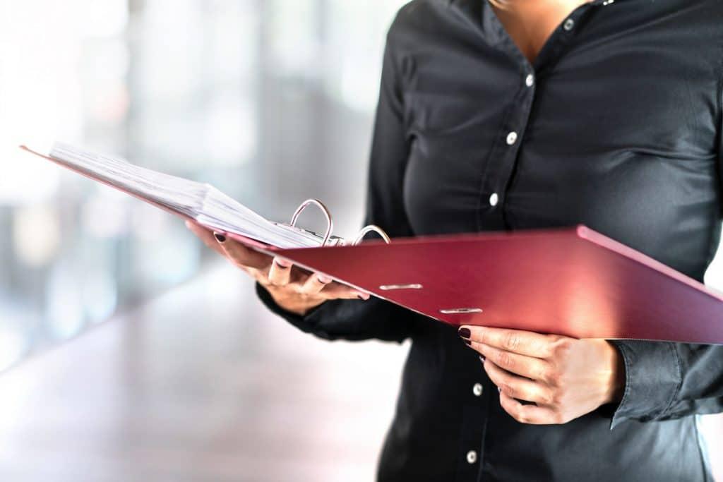 A close-up of a woman holding an open binder.