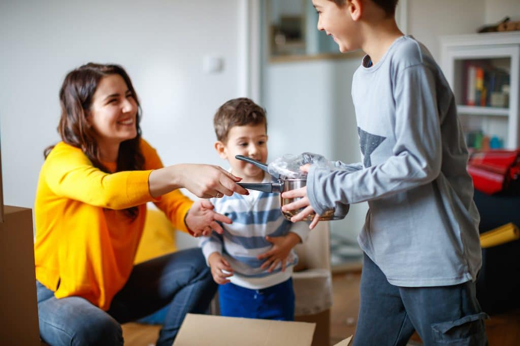 A young mom packing up pots and pans with her two children.