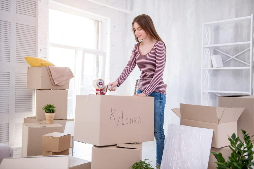 A woman taping up a moving box labeled kitchen.