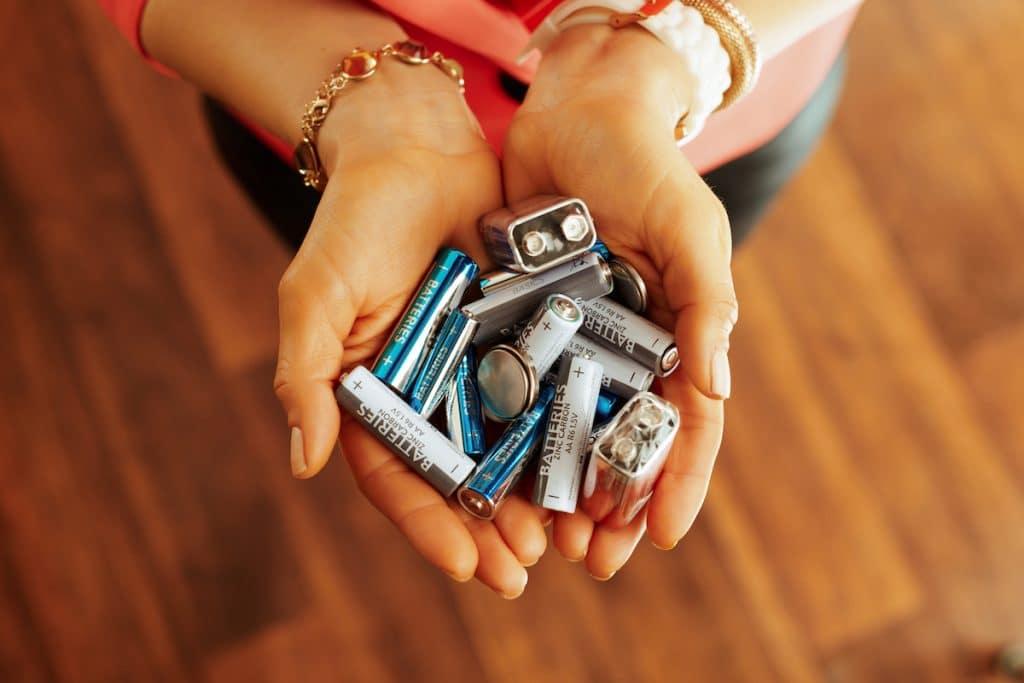 A close-up of a woman's hands holding an assortment of batteries.