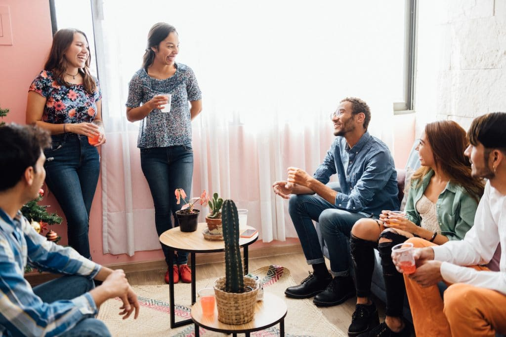 A group of friends gathering together in a living room.