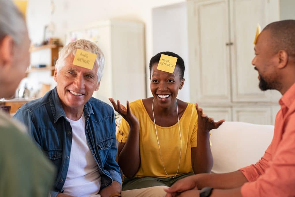 An older multi-ethnic group of friends enjoying a party game with post-it notes on their heads.